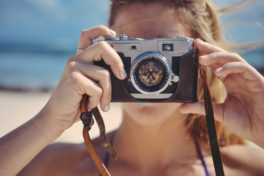 Blond Girl Taking Photo With Retro Camera In The Sun